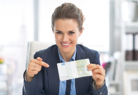 frugality: Happy business woman pointing on money pack