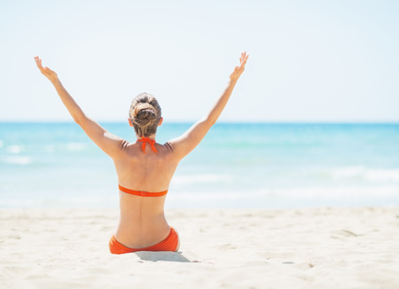 Young woman sitting on beach and rejoicing. rear view