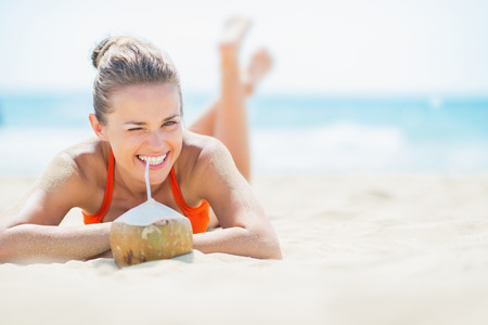 Young woman laying on beach and drinking coconut milk Stock Photo - 27036035