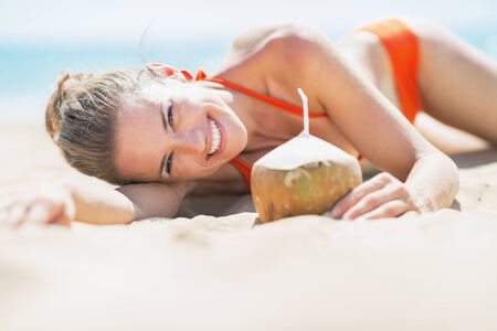 Happy young woman laying on beach with coconut Stock Photo - 27036036