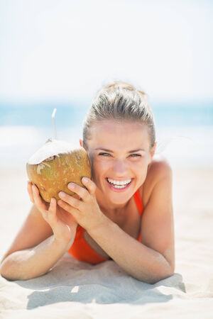 Portrait of young woman with coconut on beach Stock Photo - 27036037
