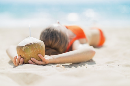 Young woman with coconut relaxing on beach Stock Photo - 27036039