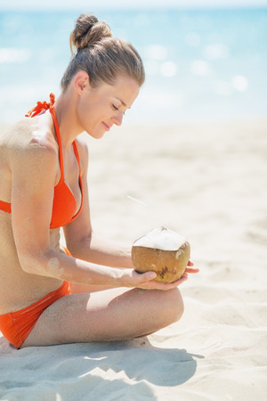 Happy young woman with coconut on beach Stock Photo - 27036040