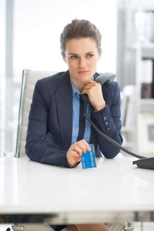 Thoughtful business woman with credit card and phone Stock Photo - 27036041