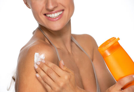 Closeup on happy young woman applying sun screen bottle photo