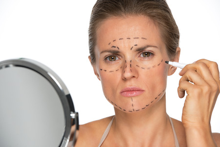 disquieted: Concerned young woman applying plastic surgery marks