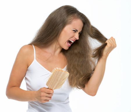 Stressed young woman combing hair Stock Photo