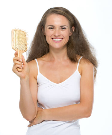 Portrait of happy young woman with hairbrush Stock Photo - 27139697