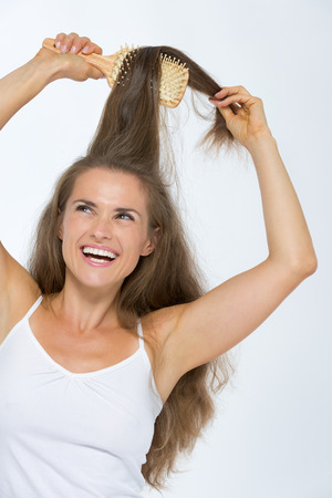 Happy young woman combing hair Stock Photo - 27139699