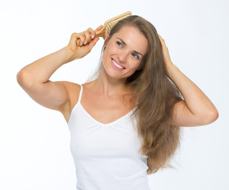 Happy young woman combing hair Stock Photo - 27139700