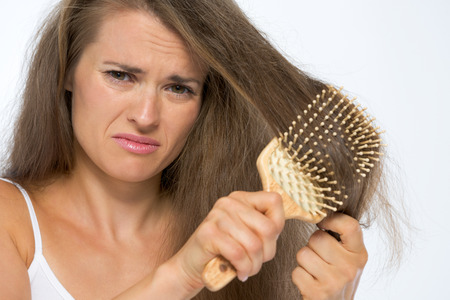 Frustrated young woman combing hair photo