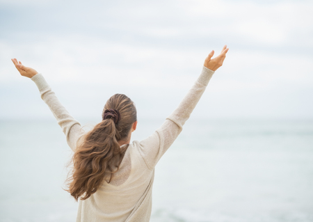 Young woman on cold beach rejoicing success. rear view Stock Photo