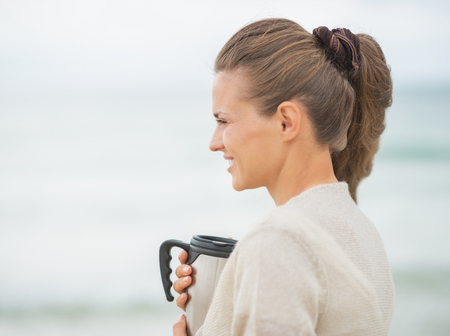 Happy young woman on cold beach with cup of hot beverage photo