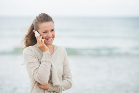 Smiling young woman talking cell phone on cold beach photo