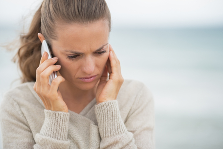 disquieted: Concerned young woman talking cell phone on cold beach Stock Photo