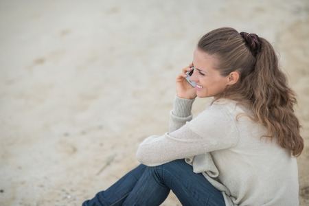 Happy young woman sitting on cold beach and talking mobile phone photo