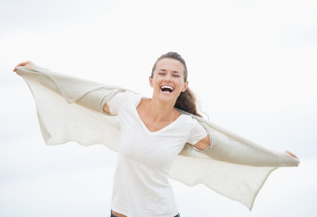 rejoicing: Happy young woman on cold beach rejoicing