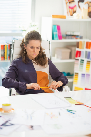 disquieted: Concerned fashion designer in office
