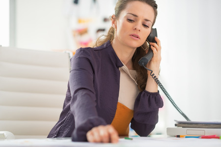 disquieted: Concerned fashion designer talking phone in office