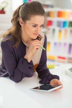 Happy fashion designer using tablet pc at work photo