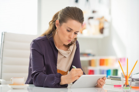 Fashion designer working on tablet pc in office Stock Photo - 27226004