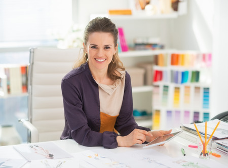 Happy fashion designer with tablet pc in office Stock Photo - 27226005