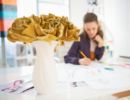 Closeup on vase of flowers on table and fashion designer working in background Stock Photo - 27221497