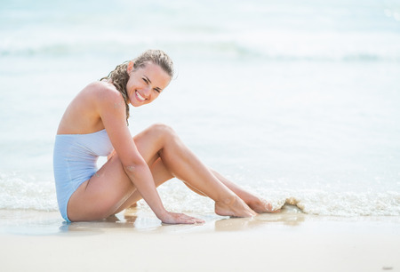 Happy young woman in swimsuit sitting on sea coast Stock Photo - 27444280