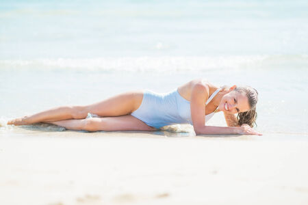 Happy young woman in swimsuit laying on sea shore Stock Photo - 27444282