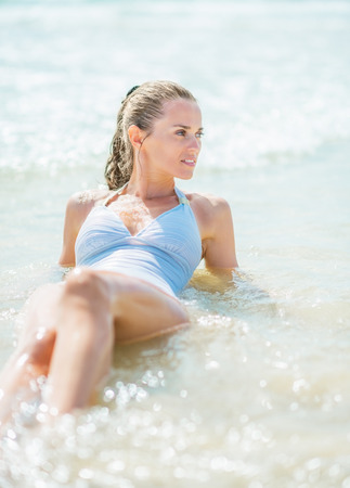 Happy young woman in swimsuit laying at seaside Stock Photo - 27444283