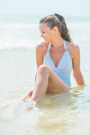 Happy young woman in swimsuit sitting in water at seaside photo