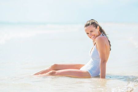 Smiling young woman in swimsuit sitting in water at seaside Stock Photo - 27444442