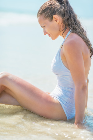 Relaxed young woman in swimsuit sitting in water at seaside Stock Photo - 27444392