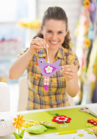 workroom: Closeup on happy young woman showing easter decoration