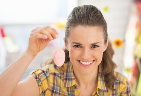workroom: Portrait of smiling young woman showing easter decorative egg