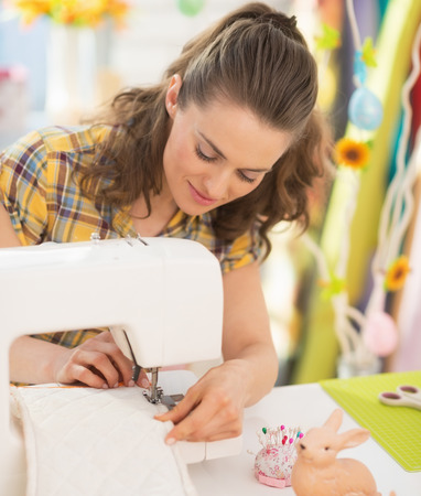 workroom: Young woman making easter pot holder mitts Stock Photo
