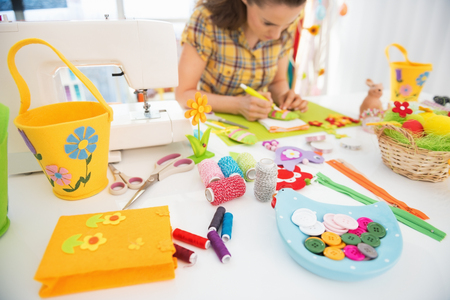 Closeup on threads and buttons on table and young woman making easter decoration in background Stock Photo - 27518688
