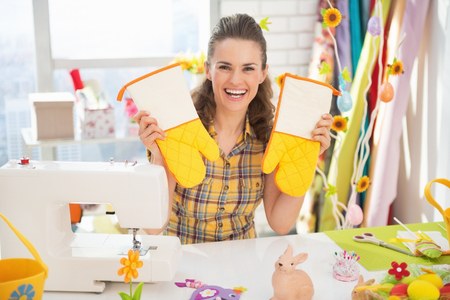 Happy young woman showing easter hand made pot holder mitts Stock Photo - 27518692