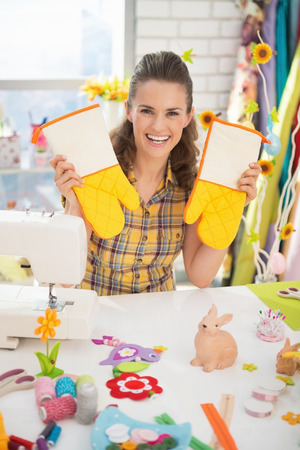 Happy young woman showing easter hand made pot holder mitts Stock Photo - 27518693
