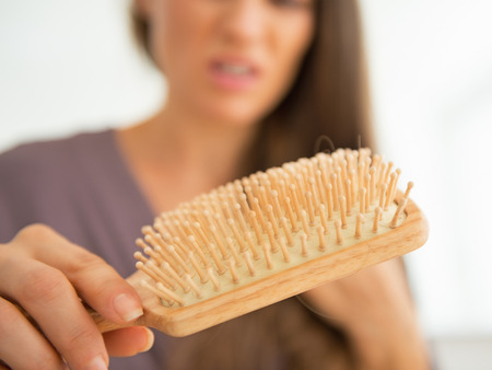 Closeup on stressed young woman looking on hair comb Reklamní fotografie