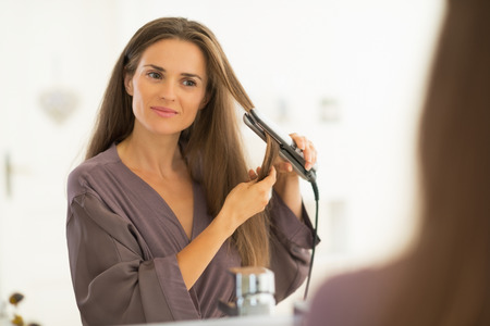 hair dressing: Young woman straightening hair in bathroom Stock Photo
