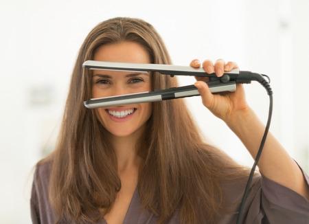 Mujer joven feliz mirando a través de plancha de pelo