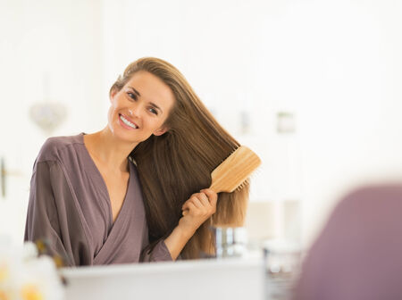 comb hair: Smiling young woman combing hair in bathroom