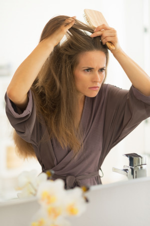 disquieted: Concerned young woman combing hair in bathroom