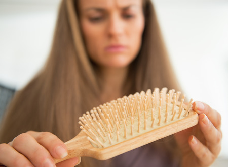 disquieted: Closeup on concerned young woman looking on hair comb