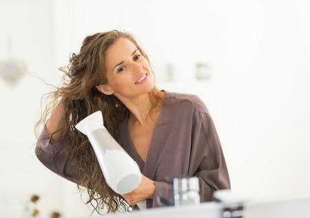 Gelukkige jonge vrouw föhnen haren in de badkamer