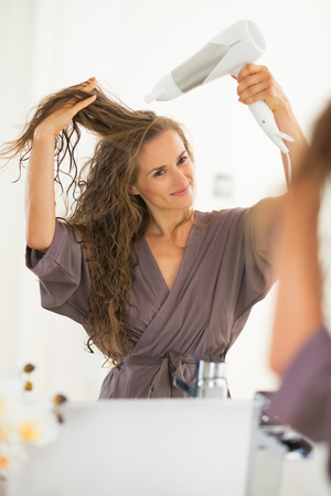 Happy young woman blow drying hair in bathroom photo