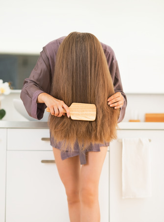Young woman combing hair in bathroom Stock Photo