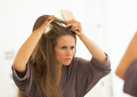 かかわっている若い女性の浴室で髪をとかす