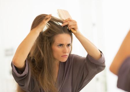 Bezorgd jonge vrouw haren kammen in de badkamer